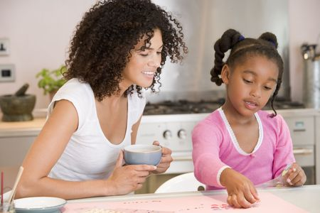 african american mother and daughter: Woman and young girl in kitchen with art project smiling