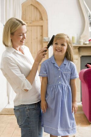 Woman in front hallway brushing young girl's hair and smiling Stock Photo - 3603654