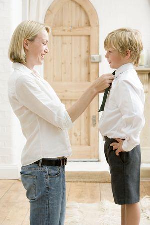 Mujer en el pasillo frente a la fijación de los jóvenes del niño corbata y sonriente