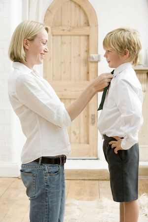 Woman in front hallway fixing young boys tie and smiling photo