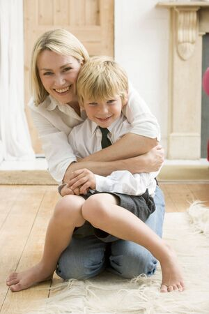 cuddling: Woman in front hallway hugging young boy and smiling