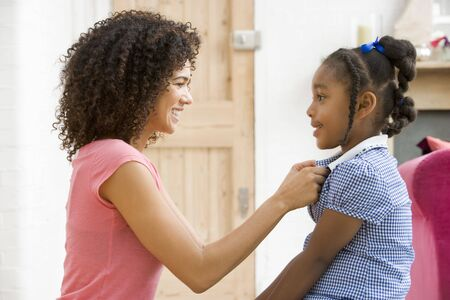 Woman in front hallway fixing young girl's dress and smiling Stock Photo - 3603026