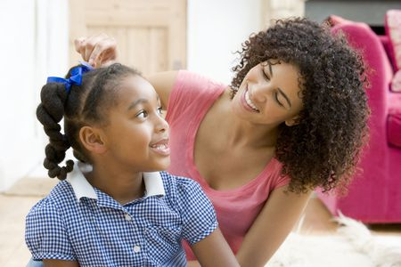 Woman in front hallway fixing young girls hair and smiling photo
