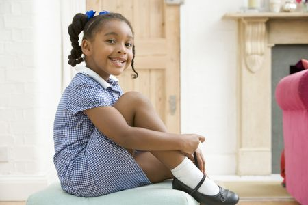Young girl in front hallway fixing shoe and smiling photo
