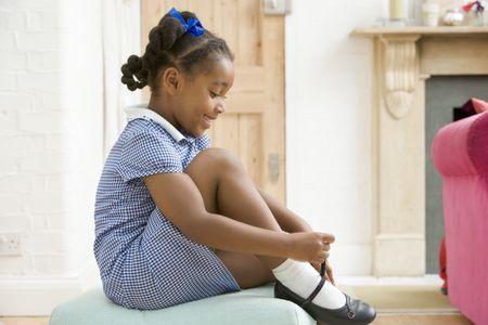 schoolgirl uniform: Young girl in front hallway fixing shoe and smiling