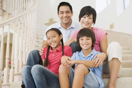 asian man smiling: Family sitting on staircase smiling
