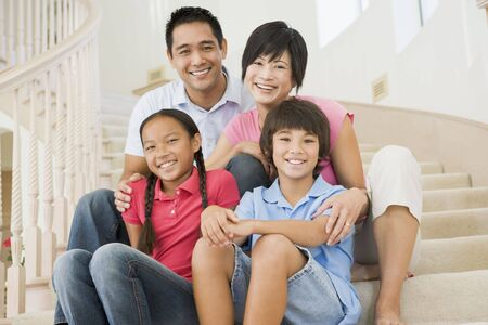 happy asian family: Family sitting on staircase smiling