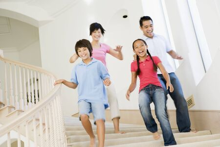 Family running down staircase smiling photo