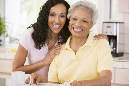 Two women in kitchen with newspaper and coffee smiling photo