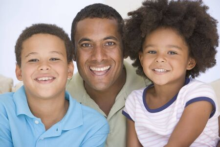 Man and two young children sitting in living room smiling photo