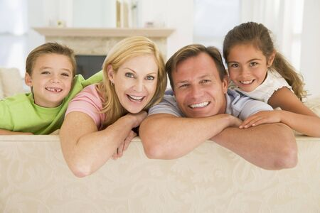 Family sitting in living room smiling Stock Photo - 3601585