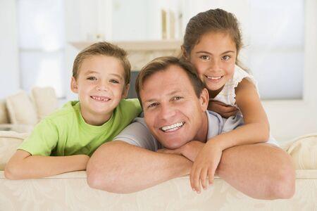bambini seduti: Uomo e due bambini seduti in salotto sorridendo