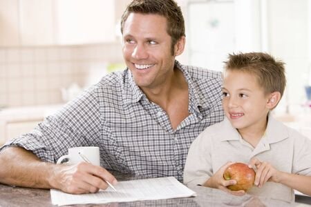 Man and young boy in kitchen with newspaper apple and coffee smiling Stock Photo - 3603705