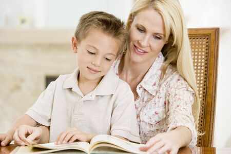 Woman and young boy reading book in dining room smiling photo