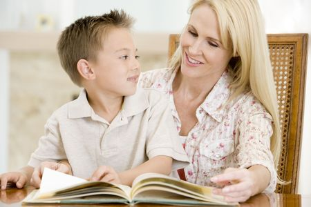 early thirties: Woman and young boy reading book in dining room smiling Stock Photo