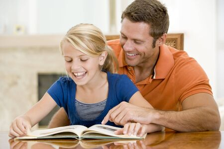 Man and young girl reading book in dining room smiling Stock Photo - 3601489