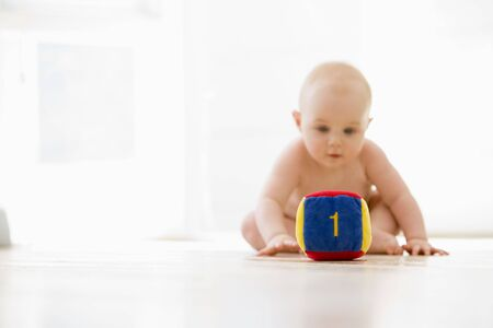 numeracy: Baby sitting indoors with block