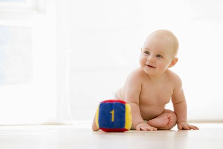 numeracy: Baby sitting indoors with block smiling