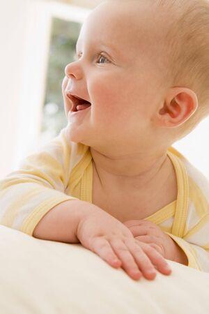 Baby lying indoors smiling photo