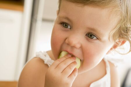 24 month old: Young girl eating apple indoors