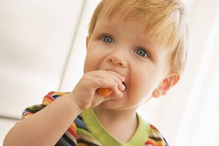24 month old: Young boy eating carrot indoors
