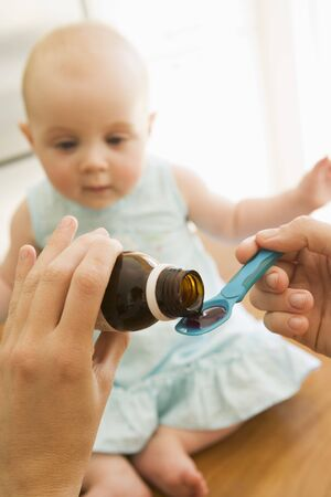 Mother giving baby medicine indoors photo