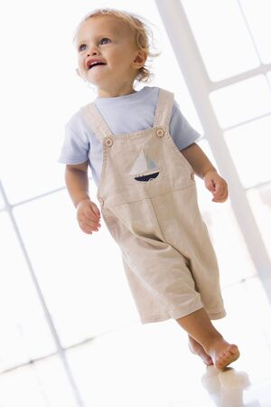 twenty four month old: Young boy walking indoors smiling