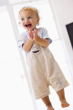 24 month old: Young boy standing indoors applauding and smiling