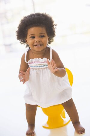 Baby indoors going on potty smiling photo