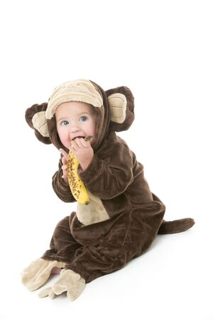 Baby in monkey costume holding banana photo