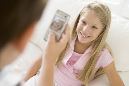 Young boy taking picture of smiling young girl with camera phone indoors photo
