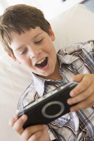 handheld: Young boy with handheld game indoors
