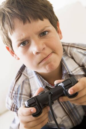 controller: Young boy holding video game controller looking confused Stock Photo
