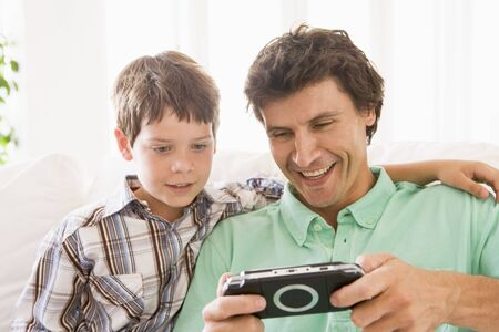 Man and young boy with handheld game smiling photo