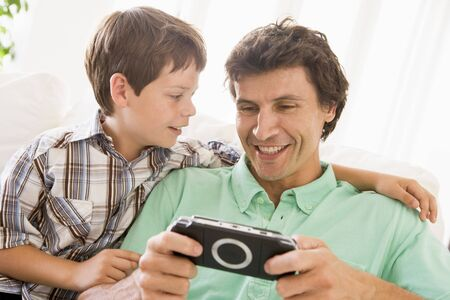 Man and young boy with handheld game smiling Stock Photo - 3603479