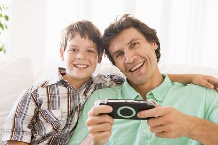 videogame: Man and young boy with handheld game smiling