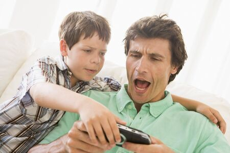 Young boy taking handheld game from unhappy man Stock Photo - 3602957