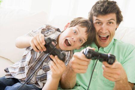 ni�os jugando videojuegos: Hombre y ni�o con los controladores de video juego sonriente  Foto de archivo