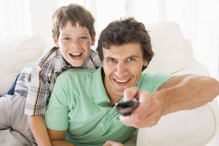 Man and young boy with remote control smiling photo