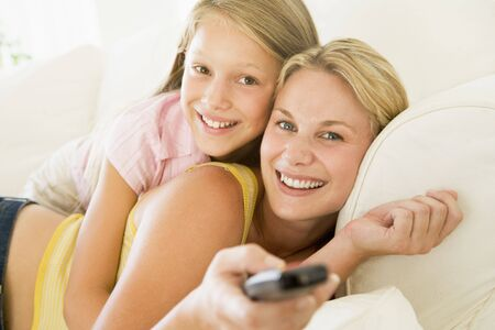 Woman and young girl with remote control embracing on sofa smiling photo