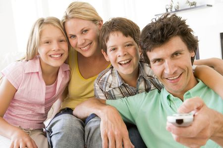 Family in living room with remote control smiling photo