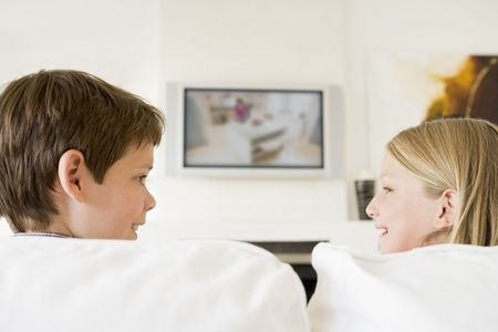 Young boy and young girl in living room with flat screen television Stock Photo - 3600747