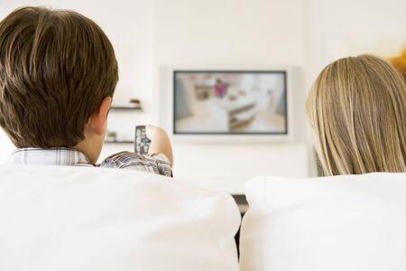 mujer viendo tv: Chico y chica en sala de estar con control remoto y pantalla plana de televisi�n