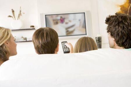 viewing: Famiglia in salotto con il controllo remoto e di televisione a schermo piatto