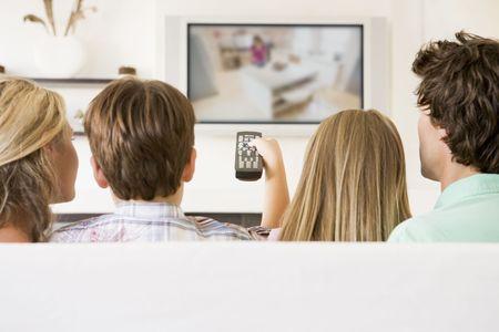 viewing: Famiglia in soggiorno con telecomando e televisione a schermo piatto