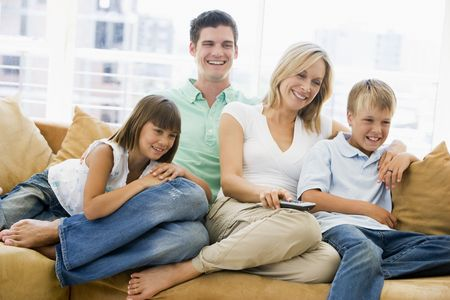 Family sitting in living room with remote control smiling Stock Photo - 3603037