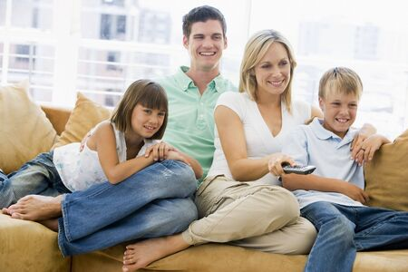 woman watching tv: Family sitting in living room with remote control smiling Stock Photo