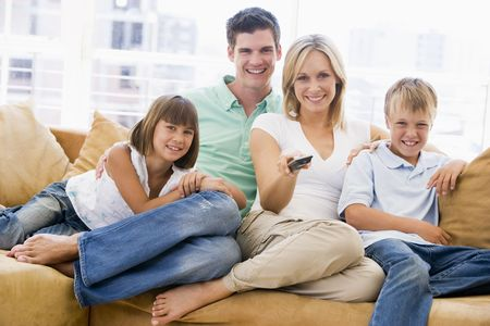 Family sitting in living room with remote control smiling photo