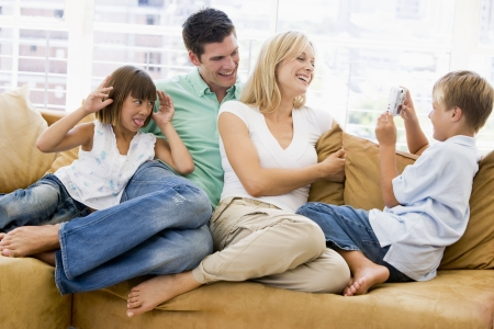 Family sitting in living room with digital camera smiling photo