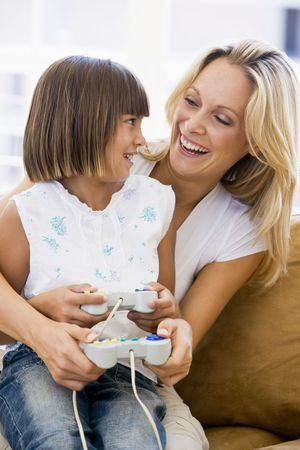 Woman and young girl in living room with video game controllers smiling photo